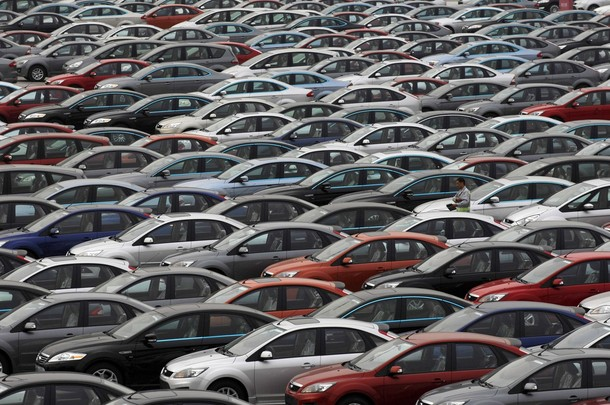 An employee walks among newly produced cars at a park of Chana Auto Co. Ltd in Chongqing Municipality
